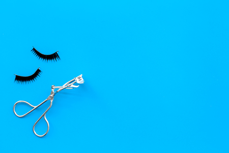 Curled and thick eyelashes. False eyelashes and eyelash curler on blue background top view copy space