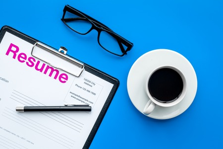 employment concept resume on pad near pen glasses coffee on