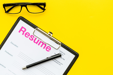 Looking for work concept. Resume on pad near pen and glasses on yellow background top view space for text Foto de archivo - 98523938