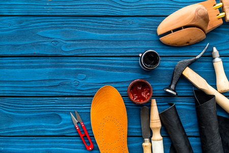 Work desk of shoemaker with instruments, wooden shoe and leather. Blue wooden background top view copy space 스톡 콘텐츠
