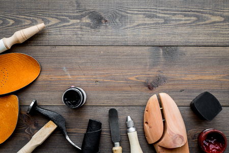 Work desk of shoemaker with instruments, wooden shoe and leather. Dark wooden background top view copy space Banco de Imagens