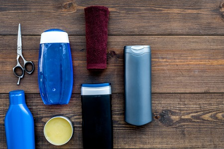 Cosmetics for mens hair. Bottles with shampoo and gel, tools for brushing on dark wooden background top view copy space Stockfoto