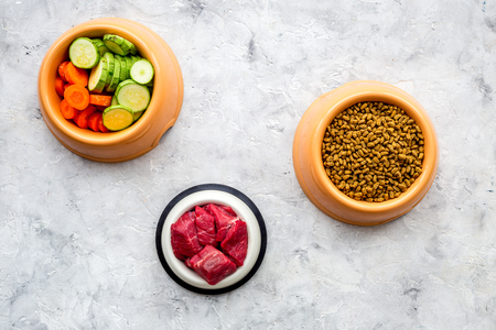 Dry pet food with natural ingredients. Raw meat, vegetables zucchini and carrot on stone table background top view.