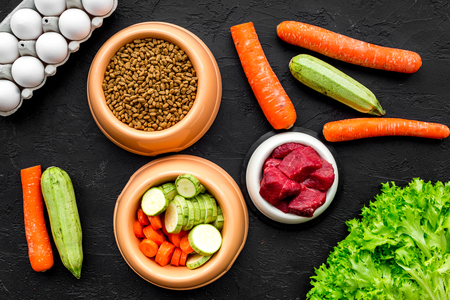 Dry pet food with natural ingredients. Raw meat, vegetables zucchini and carrot near eggs on black background top view pattern.