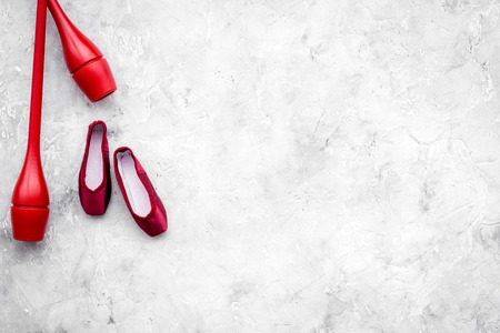 Beauty sport for girls concept. Maces for rhythmic gymnastics and ballet shoes on grey background top view. Stock Photo - 98597028