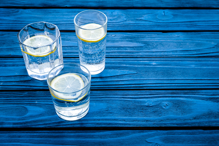 Refreshing drink. Water with lemon on blue wooden background top view.