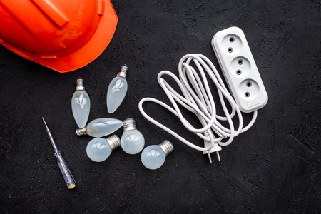 Working with electrical equipment. Hard hat, socket outlet, bulbs, screwdriver on black background top view.