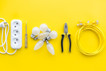 Electrical repair. Bulbs, socket outlet, cabel on yellow background top view. Foto de archivo