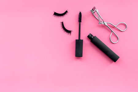 Makeup set for expressive eyelashes. Mascara, false eyelashes, eyelash curler on pink background top view.