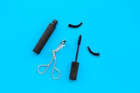 Cosmetics and tools for voluminous lashes. Mascara, false eyelashes, eyelash curler on blue background top view. 스톡 콘텐츠