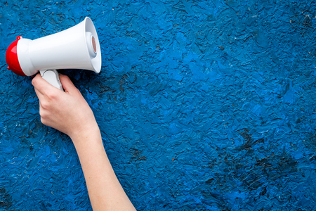 Announcement concept. Megaphone in hand on blue background top view copy space