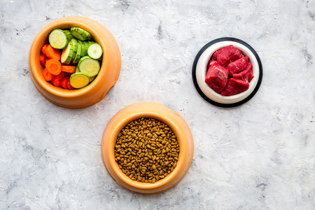 Dry pet food with natural ingredients. Raw meat, cut vegetables zucchini and carrot on stone backgroud top view copy space