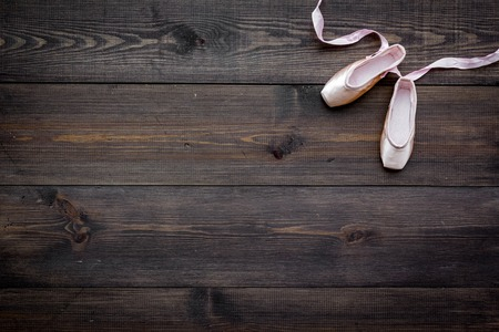 Professional dance shoes. Ballet concept. Pointes on dark wooden background top view copy space Stock Photo - 98856978