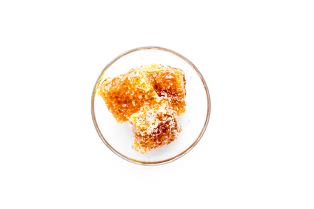 Honeycomb filled with honey on plate on white background top view space for text