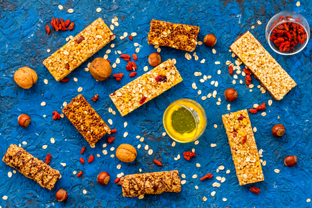 Make hearty granola bars with oatmeal, nuts, honey and berries. Blue background top view