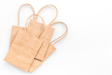 Brown kraft paper bag for shopping on white background top view copy space mockup
