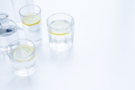 Refreshing drink. Water with lemon on white background top view copy space