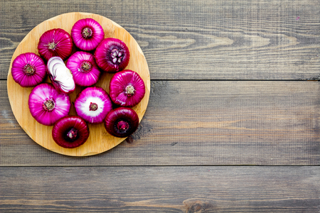 Red onion for salads on dark wooden background top view copy space