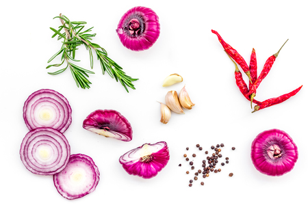 Red onion rings as seasoning. Onion near chili peper, rosemary, black peper, garlic on white background top view