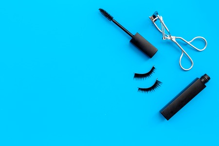 Cosmetics and tools for voluminous lashes. Mascara, false eyelashes, eyelash curler on blue background top view copy space