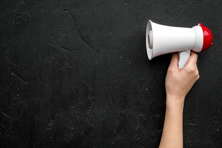 Megaphone in hand on black background top view copy space