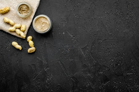 Homemade spa with organic scrub and peanut on dark background top view space for text