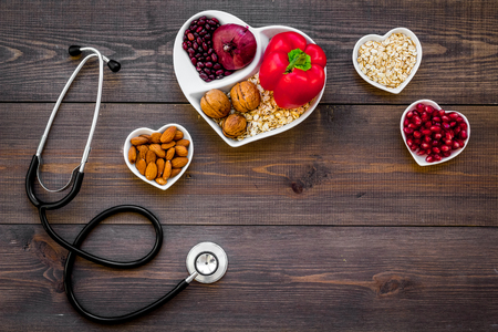 Products good for heart and blood vessels. Vegetables, fruits, nuts in heart shaped bowl near stethoscope on dark wooden background top view.