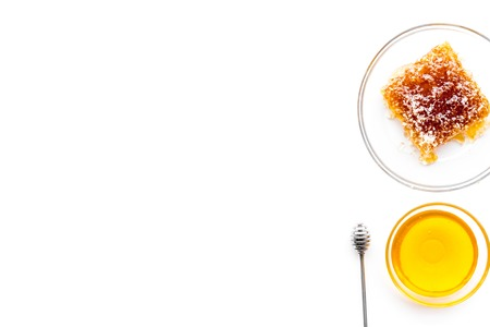 Apiary products. Honey in bowl and honeycomb on white background top view.