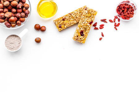 Make hearty granola bars with oatmeal, nuts, honey and berries. White background top view. 写真素材
