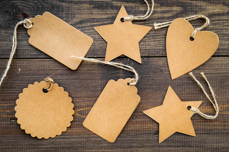 Figured blank tags for write price or discount on dark wooden background. Фото со стока