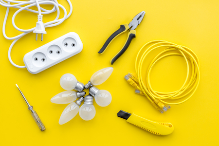 Electrical repair. Bulbs, socket outlet, cabel on yellow background top view. Imagens