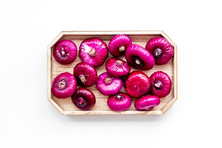 Red onion is healthy product. Onion bulbs in tray on white background top view.