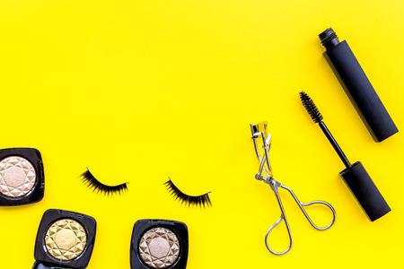 Makeup cosmetics for eyes. Eyeshadow, mascara, false eyelashes, eyelash curler on yellow background top view. Stock Photo