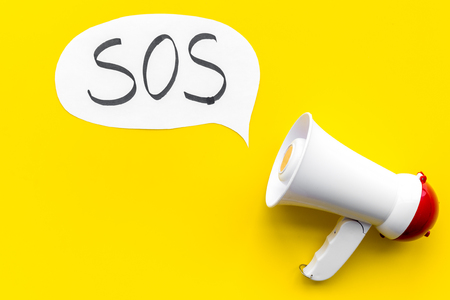 Ask for help concept. Megaphone near cloud with word SOS on yellow background top view. Stok Fotoğraf