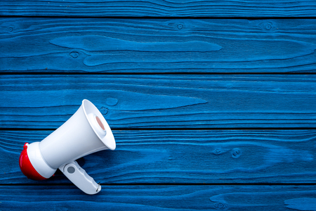 Announcement concept. Megaphone on blue wooden background top view copy space