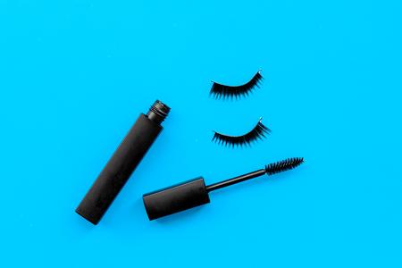 Basic products for eyelashes makeup. Mascara and false eyelashes on blue background top view copy space