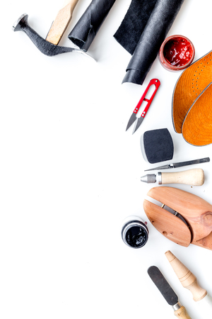 Clobber tools. Hummer, awl, knife, sciccors, wooden shoe, paint and leather. White background top view space for text