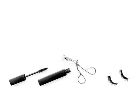 Cosmetics and tools for voluminous lashes. Mascara, false eyelashes, eyelash curler on white background top view space for text 스톡 콘텐츠