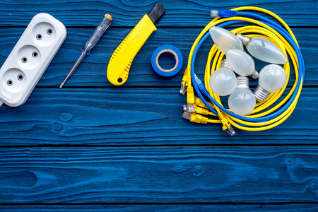 Electrical repair. Bulbs, socket outlet, cabel, screwdriver, pilers on blue wooden background top view copy space