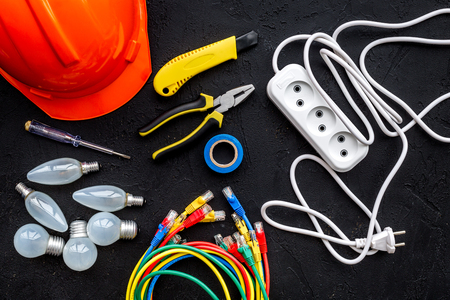 Electrician work concept. Hard hat, tools, cabel, bulb, socket outlet on black background top view