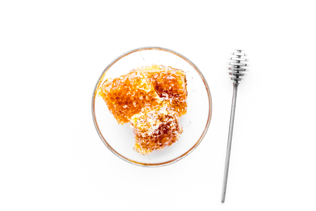 Honeycomb filled with honey on plate on white background top view
