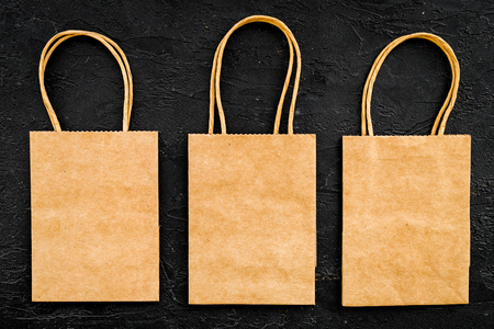 Brown kraft paper bag for shopping on black background top view.