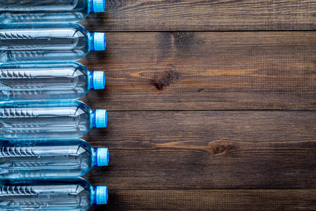 Drinking water in bottles on dark wooden background top view.