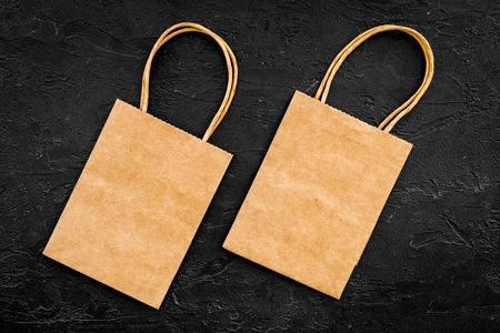 Brown kraft paper bag for shopping on black background top view mockup