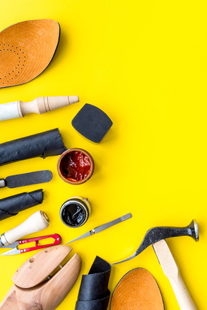 Clobber tools. Hummer, awl, knife, sciccors, wooden shoe, paint and leather. Yellow background top view space for text Stock Photo