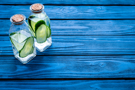 Drink for weight loss. Water with cucumber on blue wooden background top view copy space