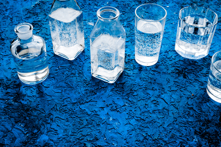 Drinks on the table. Pure water in jar and glasses on blue background space for text