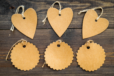 Figured blank tags for write price or discount on dark wooden background mockup pattern
