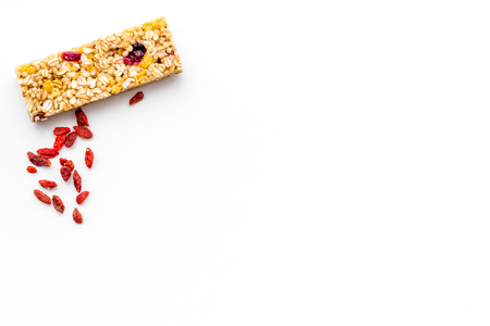 Granola bars with Goji berry on white background top view space for text