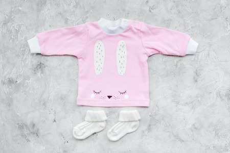 Newborn babys background. Clothes for small girl with booties on grey background top view